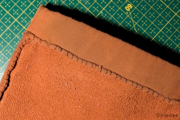 Overlockový steh - softshellové kalhoty po roce nošení, zakončení nohavice